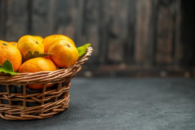 Widok z przodu świeże mandarynki w wiklinowym koszu na ciemnym wolnym miejscu