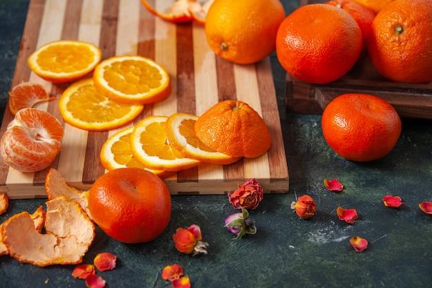 Widok z przodu świeże mandarynki z pomarańczami na ciemnych warzywach dieta sałatka napój jedzenie cytrusowy posiłek egzotyczny