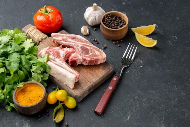 Widok z przodu świeże mięso kawałek surowego mięsa z zieleniną na ciemnym tle danie z grilla pieprz kuchnia jedzenie krowa sałatka pokarm dla zwierząt