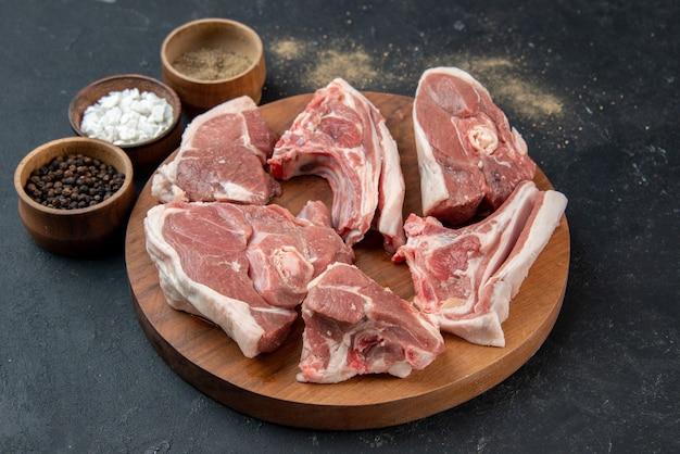 Widok z przodu świeże mięso plastry surowe mięso z przyprawami na ciemnym tle posiłek jedzenie świeżość krowa jedzenie kuchnia zwierzę