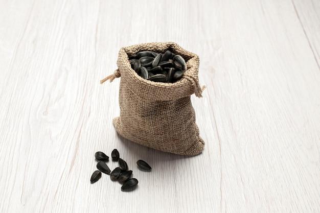 Widok z przodu świeże nasiona słonecznika czarne kolorowe nasiona w małej torebce na białym tle nasiona przekąska zdjęcie wiele olejów