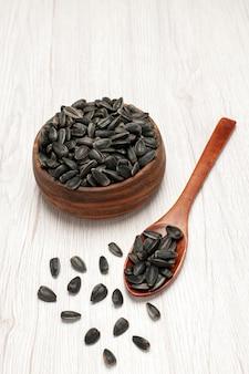 Widok z przodu świeże nasiona słonecznika czarne nasiona na białym biurku wiele worków na rośliny oleiste