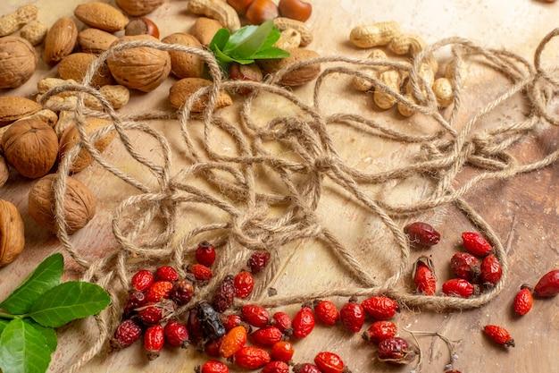 Widok z przodu świeże orzechy włoskie z orzechami laskowymi i orzeszkami ziemnymi na drewnianym biurku orzech orzech