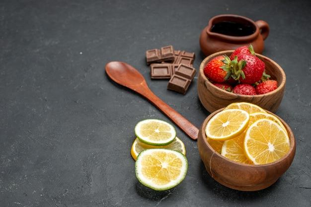 Widok z przodu świeże owoce, truskawki i cytryny na szarym tle