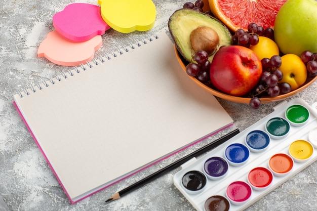 Widok z przodu świeże owoce winogrona brzoskwinia i awokado wewnątrz płyty z notatnikiem na białej powierzchni