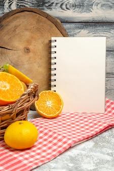 Widok z przodu świeże owoce winogrona i pokrojone pomarańcze w koszu na szarym tle owoce dojrzałe aksamitne witaminy świeże