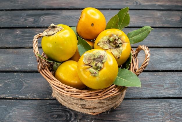 Widok z przodu świeże persimmons dojrzałe słodkie owoce na drewnianym biurku owoce łagodne dojrzałe drzewo