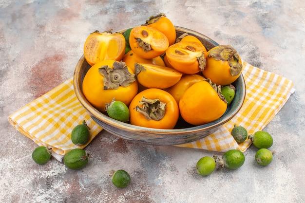 Widok z przodu świeże persimmons w misce żółty ręcznik kuchenny feijoa na nagim tle