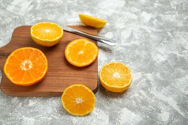Widok z przodu świeże pokrojone pomarańcze łagodne cytrusy na białym tle dojrzałe owoce egzotyczne świeże tropikalne