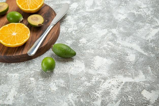 Widok z przodu świeże pokrojone pomarańcze z feijoa na białym tle dojrzałe owoce egzotyczne tropikalne świeże