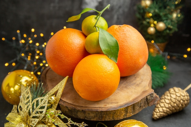 Widok z przodu świeże pomarańcze wokół świątecznych zabawek na ciemnym tle owoce tropikalne egzotyczne świeże soki