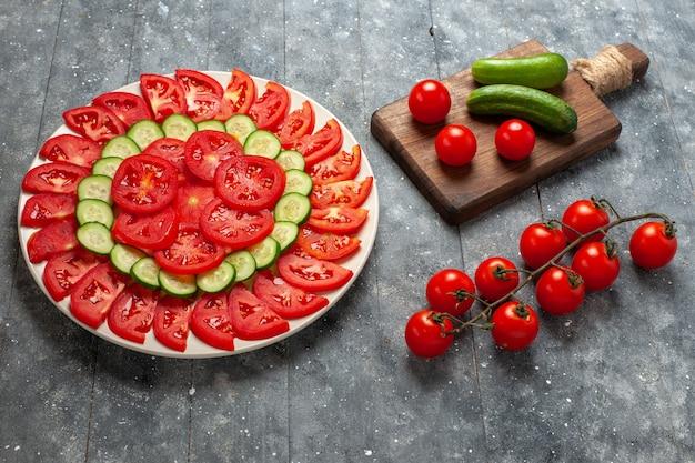Widok z przodu świeże pomidory w plasterkach elegancko zaprojektowana sałatka na szarej rustykalnej przestrzeni