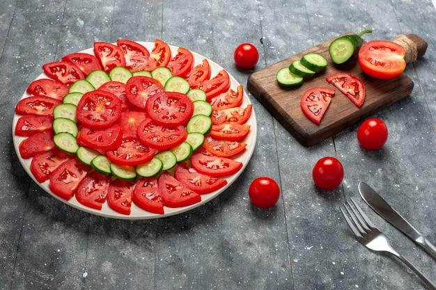 Widok z przodu świeże pomidory w plastrach elegancko zaprojektowane z ogórkami na szarej rustykalnej przestrzeni