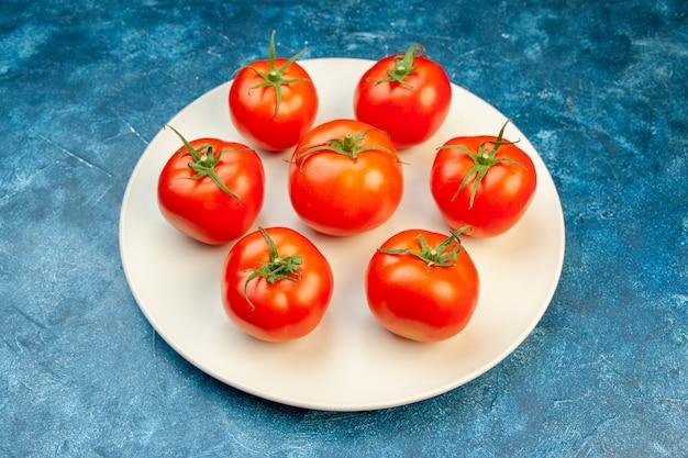 Widok z przodu świeże pomidory wewnątrz talerza na niebieskich dojrzałych warzywach w kolorze czerwonym sałatka z drzewa
