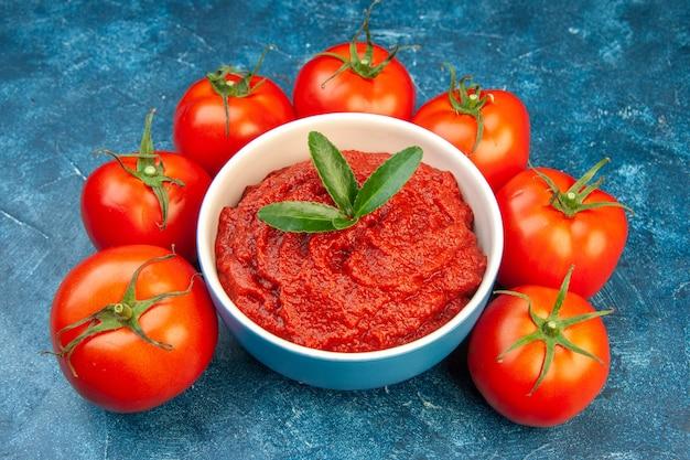 Widok z przodu świeże pomidory z pastą pomidorową na niebieskiej sałatce czerwone drzewo warzywo kolor dojrzałe jedzenie