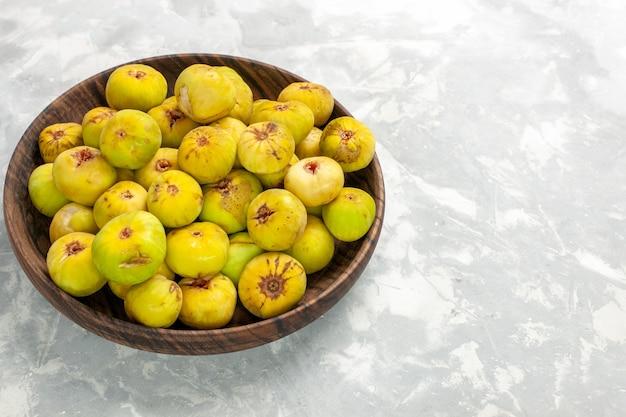 Widok z przodu świeże słodkie figi wewnątrz brązowego talerza na lekkim biurku