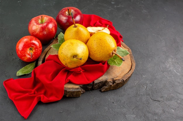 Widok z przodu świeże słodkie gruszki z jabłkami na ciemnym stole dojrzały świeży, łagodny kolor