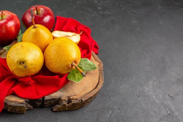 Widok z przodu świeże słodkie gruszki z jabłkami na ciemnym stole świeży kolor dojrzały aksamitny