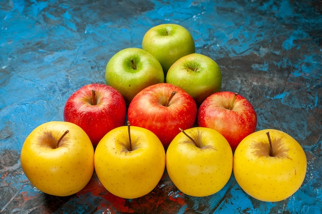 Widok z przodu świeże słodkie jabłka wyłożone trójkątem na niebieskim tle dieta witamina smaczne dojrzałe łagodne zdrowie