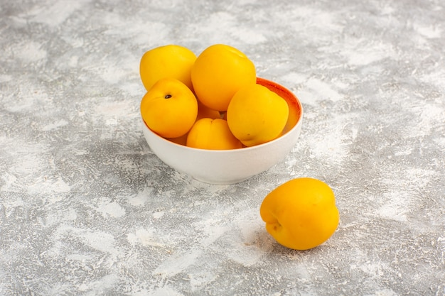 Widok z przodu świeże słodkie morele żółte owoce na białej powierzchni