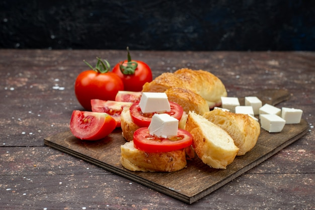 Widok z przodu świeże smaczne pieczywo długie drożdżówka uformowane krojone ciasto z serem i pomidorami na brązowo