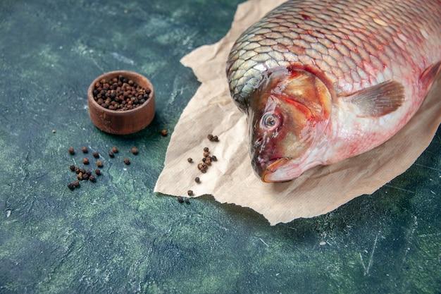 Widok z przodu świeże surowe ryby z pieprzem na ciemnoniebieskiej powierzchni mięso woda ocean kolor poziomy posiłek żywności z owoców morza