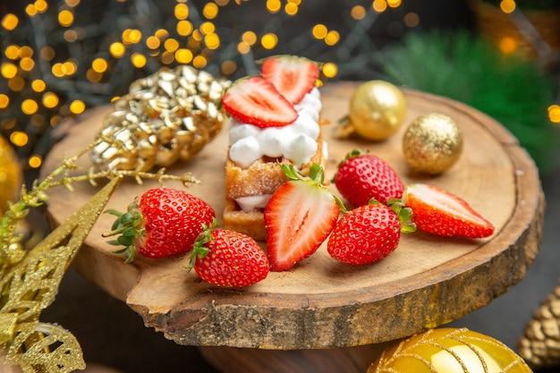 Widok z przodu świeże truskawki wokół świątecznych zabawek na ciemnym tle owocowy smak świąteczne zdjęcie ciemne