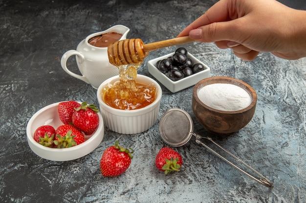 Widok z przodu świeże truskawki z miodem na ciemnej powierzchni owoce słodkie galaretki jedzenie