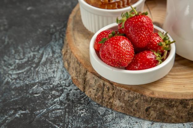 Widok z przodu świeże truskawki z miodem na ciemnej powierzchni słodka galaretka owocowa