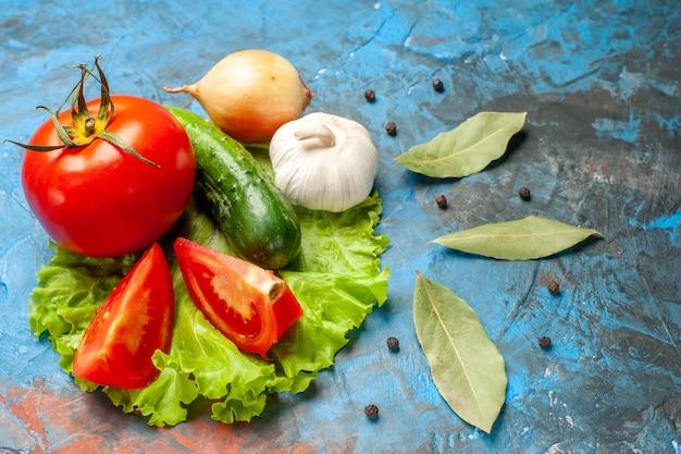 Widok z przodu świeże warzywa ogórek z zieloną sałatą z pomidorów i czosnkiem na niebieskim tle sałatka z mąką zdrowie dojrzałe jedzenie dieta kolor