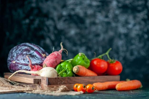 Widok z przodu świeże warzywa rzodkiewki pomidory marchewki i kapusta na ciemnym tle zdrowie kolor żywności warzywo sałatka mączka roślinna