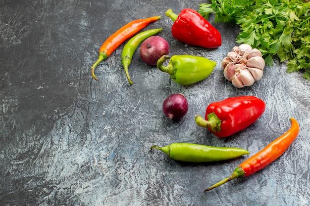 Widok z przodu świeże warzywa z papryką i czosnkiem na jasnoszarej sałatce posiłek zdjęcie danie jedzenie zdrowe życie kolory