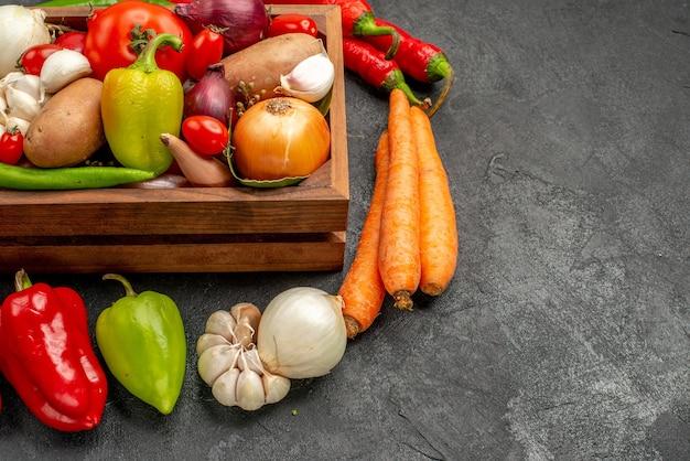 Widok z przodu świeże warzywa z pieprzem i czosnkiem na ciemnym stole dojrzała kolorowa sałatka zdrowie