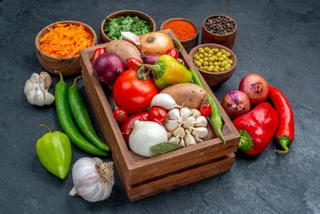 Widok z przodu świeże warzywa z zieleniną na ciemnym stole dojrzała sałatka w kolorze warzyw