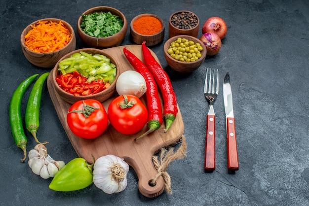 Widok z przodu świeże warzywa z zieleniną na ciemnym stole sałatka z dojrzałych warzyw