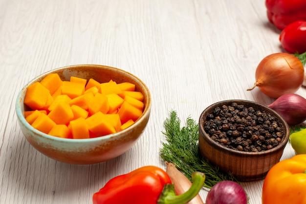 Widok z przodu świeże warzywa z zieleniną na jasnym białym biurku sałatka dojrzała dieta zdrowotna