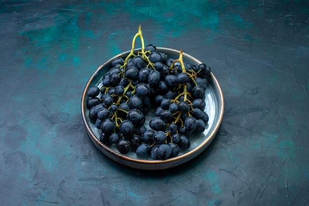 Widok z przodu świeże winogrona czarne winogrona na ciemnym biurku