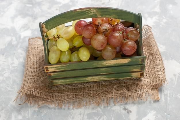 Widok z przodu świeże winogrona soczyste i łagodne owoce na białej powierzchni