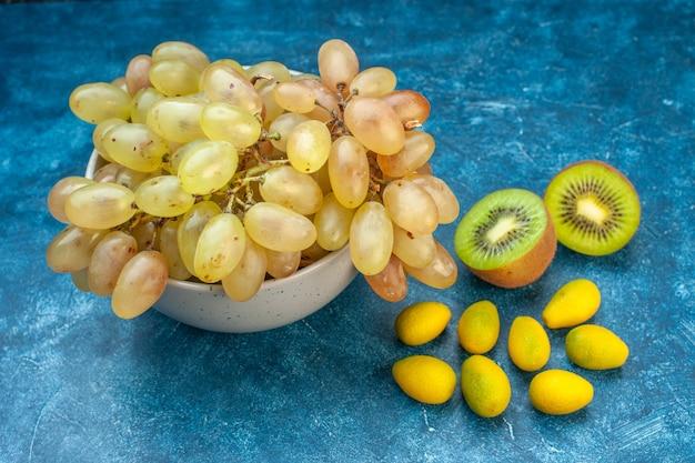 Widok z przodu świeże winogrona wewnątrz talerza na niebieskim, dojrzałym kolorze soku owocowego
