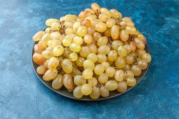 Widok z przodu świeże winogrona wewnątrz talerza na niebieskim kolorze drzewa łagodne kwaśne zdrowie egzotyczne zdjęcie owoców