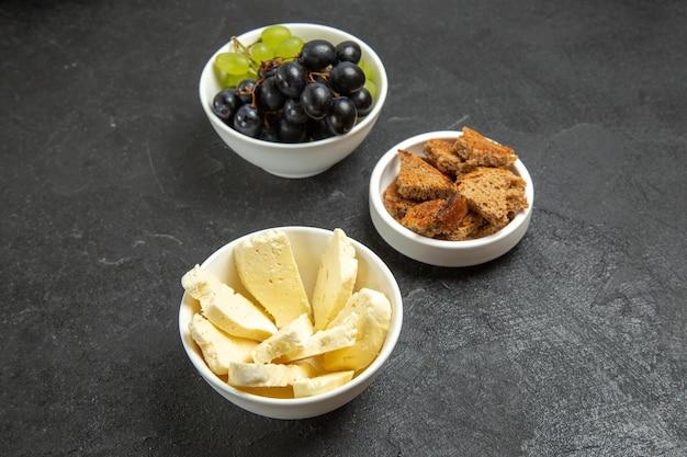 Widok z przodu świeże winogrona z białym serem i pokrojonym ciemnym chlebem na ciemnym biurku posiłek jedzenie danie mleko owoce