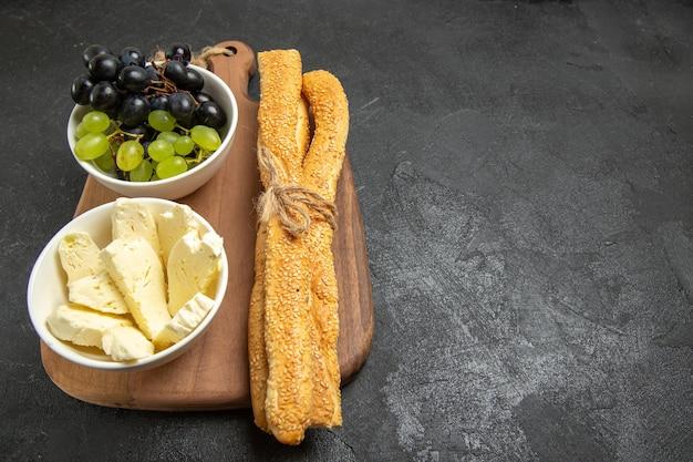 Widok z przodu świeże winogrona z serem i chlebem na ciemnym tle owoce łagodne dojrzałe drzewo witamina jedzenie mleko