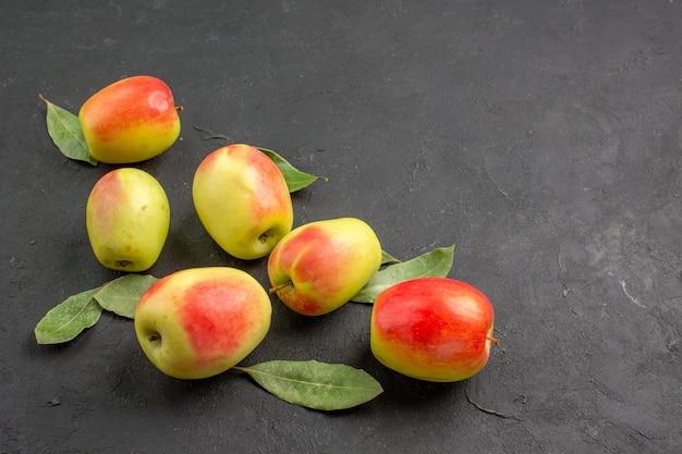 Widok z przodu świeże zielone jabłka z zielonymi liśćmi na ciemnym drzewie stołowym łagodnie dojrzałe świeże