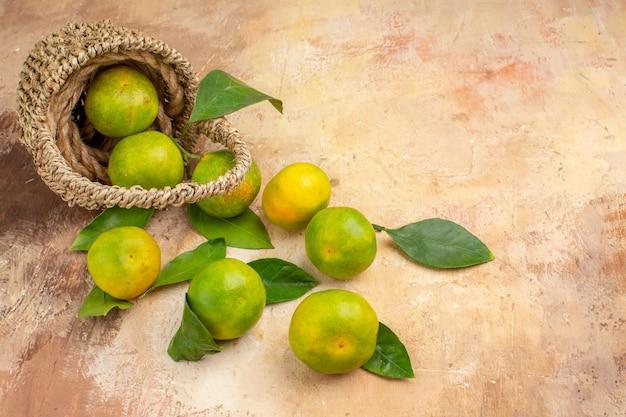 Widok z przodu świeże zielone mandarynki w koszu na jasnym tle zdjęcia w kolorze łagodnego soku owocowego