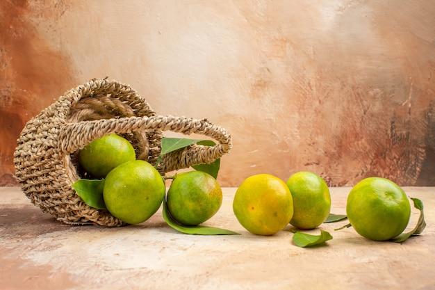 Widok z przodu świeże zielone mandarynki wewnątrz kosza na jasnym biurku zdjęcie w kolorze łagodnego soku owocowego