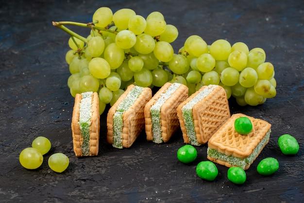 Widok z przodu świeże zielone winogrona kwaśne soczyste i łagodne z ciasteczkami na ciemnym tle dojrzałe zielone owoce roślin