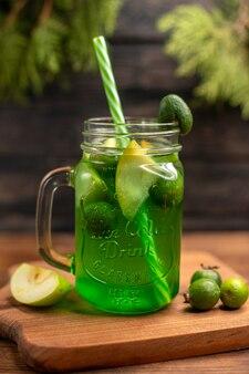 Widok z przodu świeżego soku owocowego w szklance podawanego z rurkami i feijoas z limonek jabłkowych na drewnianej desce do krojenia