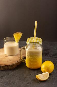 Widok z przodu świeży koktajl pyszny napój chłodzący w środku puszka ze słomką w pobliżu drewnianego biurka wraz z cytrynami na ciemnym tle pij letni sok