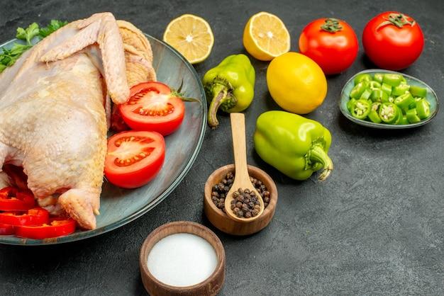 Widok z przodu świeży kurczak z zieleniną cytryną i warzywami na ciemnym tle ptak jedzenie kolor mięso zwierzę