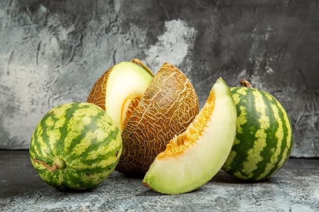 Widok z przodu świeży melon z arbuzem na ciemnym tle światła